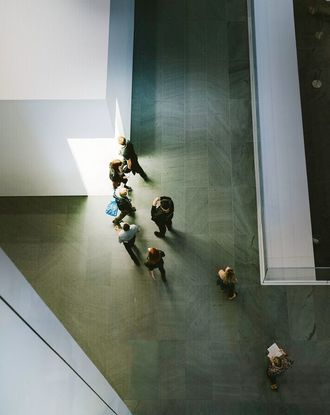 Aerial view of people standing and walking in front on white concrete building