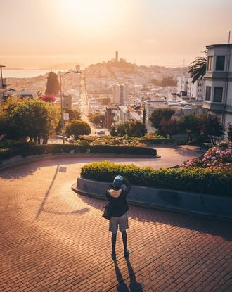 Person taking photo of building during sunset on Lombard Street