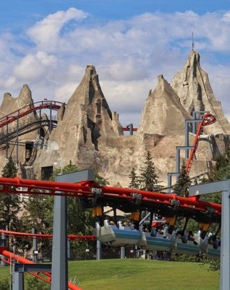Red rollercoaster ride in Canada's Wonderland in front of mountains