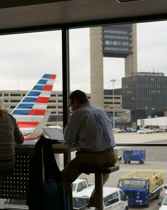 People waiting in airport lounge by windows overlooking planes