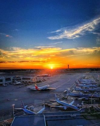 Parked airplanes at the Miami International Airport with the sun setting in the background