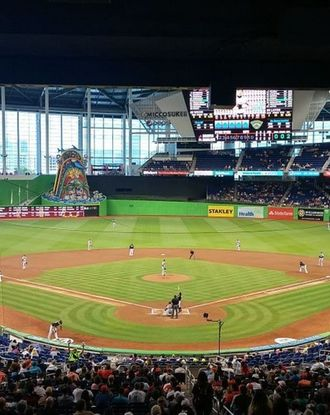 Baseball players playing a game in the the Marlins Park stadium