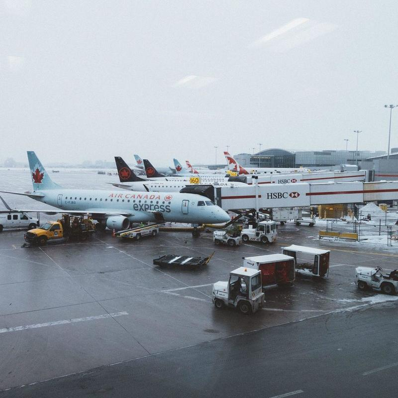 Airplanes parked at airport dock during a foggy day