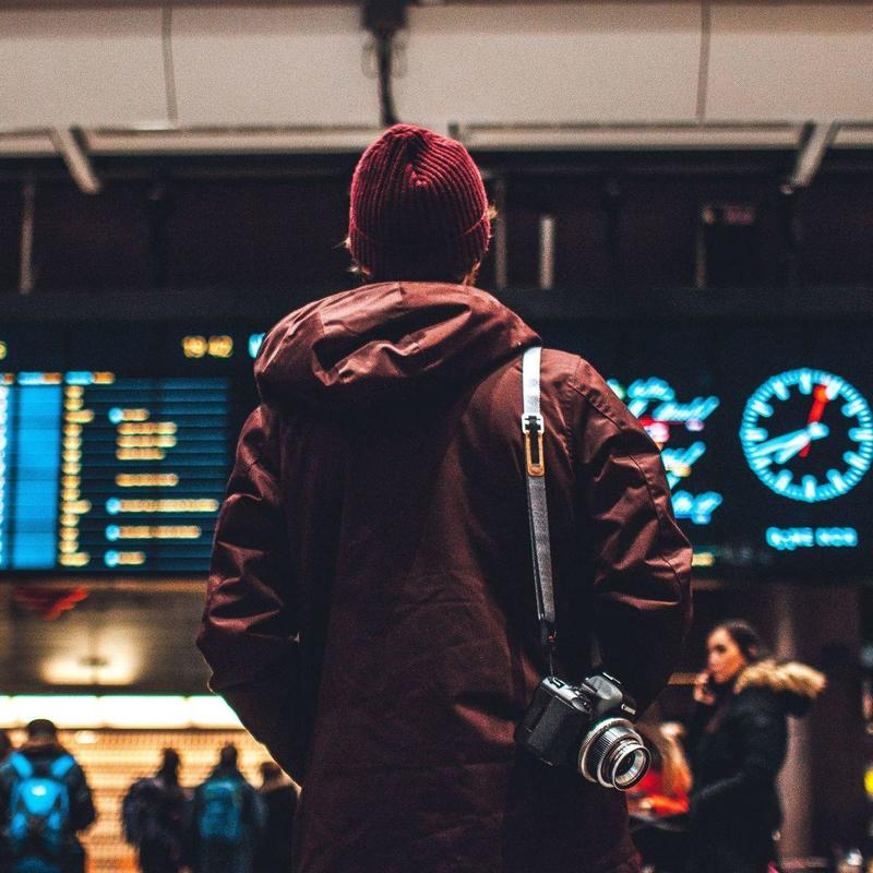 Man with beanie looking at airport schedule